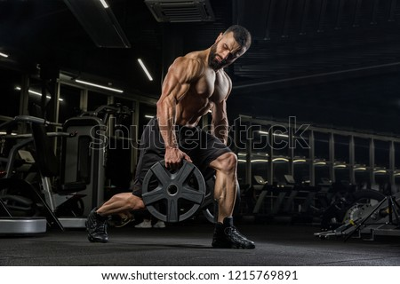 Attractive tall muscular bodybuilder doing heavy deadlifts in moder fitness center.