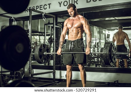 Attractive tall muscular bodybuilder doing heavy deadlifts in moder fitness center. Toned image.