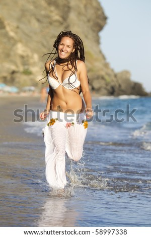 Attractive tanned girl running along the beach