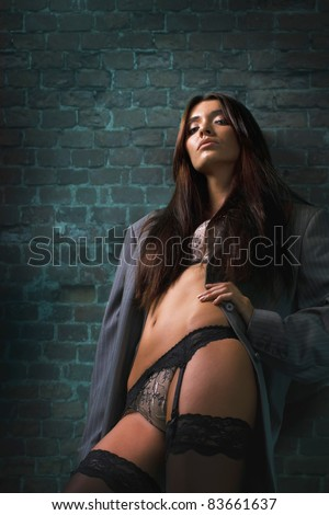 Attractive tanned toll brunette model in sexy lingerie, stockings and men's jacket posing against brick wall