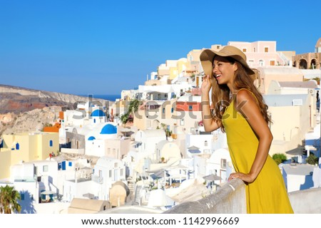 Attractive tanned woman in Oia village repairs herself with hat from the sun when looking cityscape from balcony in Santorini Island, Greece #1142996669