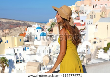Attractive tanned woman in Oia village repairs herself with hat from the sun when looking cityscape from balcony in Santorini Island, Greece #1199779771