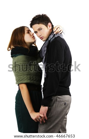 Attractive teen age girl leaning to kiss a fashion model on the cheek isolated on white background