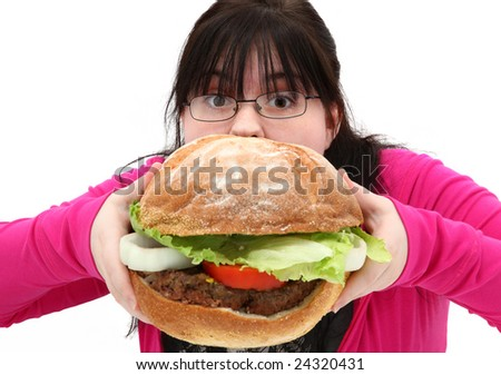Attractive teen girl eating giant hamburger over white with funny expression.