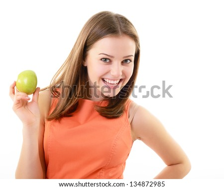 Attractive teen girl holding an apple in her hand and happy smiling, looking at camera. Face closeup over white background