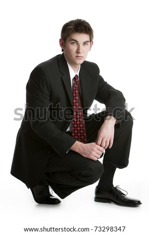 Attractive teenage boy kneeling in a suit isolated on white background