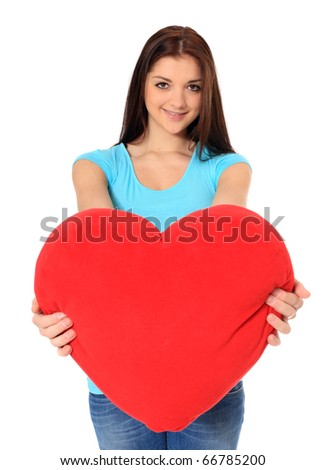 Attractive teenage girl holding red heart-shaped pillow. All on white background.