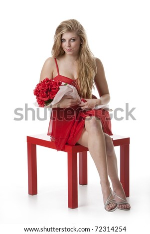 Attractive teenage girl in a red dress holding a bouquet of roses sitting on red table