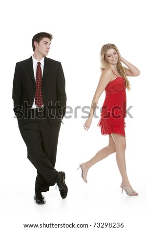 Attractive teenage girl in a red dress walking away from teenage boy in a suit