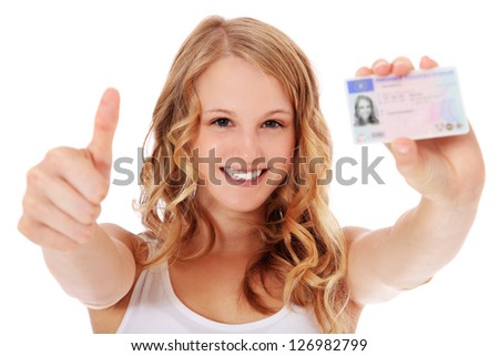 Attractive teenage girl proudly showing her drivers license. All on white background.