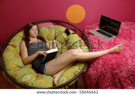 Attractive teenage girl reads book in her room.