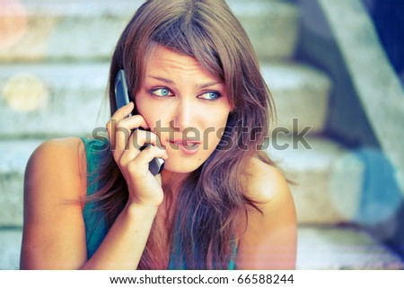 Attractive teenage girl with problems talking by phone. She worried, and she is in frustration.