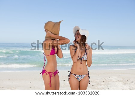 Attractive teenagers standing in swimsuit while holding her hats