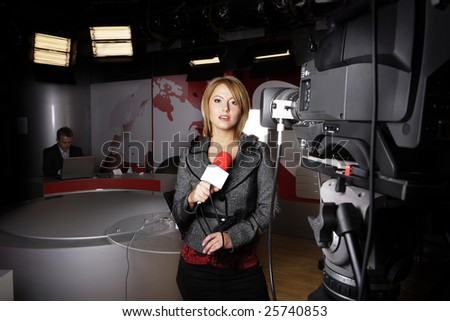 attractive television news presenter standing in front of the video camera