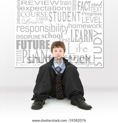 Attractive ten year old american boy in big baggy sit sitting in front of educational themed words hanging on wall.