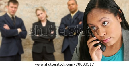 Attractive thirty something business woman on cordless phone.  Business team in background.