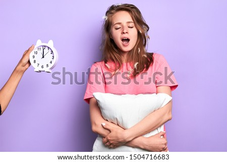 Attractive tired young woman yawning broadly with closed eyes, happy its time to go to bed, exhausted after long hard day, invisible person holding alarm clock showing late night time.