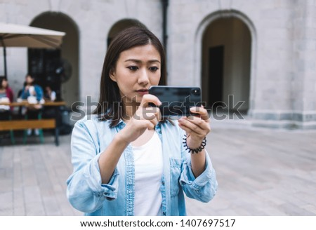 Attractive tourist taking pictures and shooting video on mobile phone for publication in internet networks via 4G internet standing in historic center with public wifi, Asian woman clicking images #1407697517