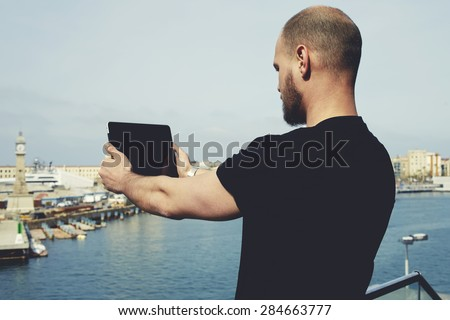 Attractive tourist with digital tablet camera taking picture of beautiful city from viewpoint, young handsome man photographing marina port city with touch pad,male enjoying vacation journey in summer