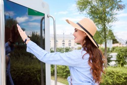 Attractive tourist woman touches the screen of the information stand. Pretty woman is wearing wide brimmed hat and casual blue shirt. Summer vacation.