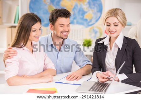 Attractive travel agent showing catalog with tours to happy young couple.