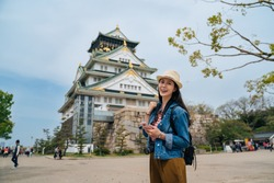attractive traveler standing in front of osaka castle using phone searching the entrance fee. young woman tourist joyful face camera smiling on sunny day. beautiful lady holiday lifestyle.