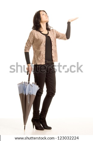 Attractive trendy woman worried about the rain holding out her hand and looking up at the sky while holding a closed umbrella in the other hand, full length studio portrait isolated on white