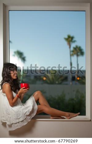 Attractive twenties hispanic brunette woman relaxing lifestyle sitting by window