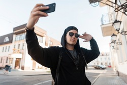 Attractive urban young hipster man in black fashionable clothes in a trendy cap in sunglasses walks through the city and takes a selfie on the phone. Handsome guy posing near a vintage building.