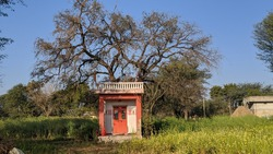 Attractive view of Hindu God temple in a Indian farmland. Sign of devotee and universal power. Devotee temple concept.