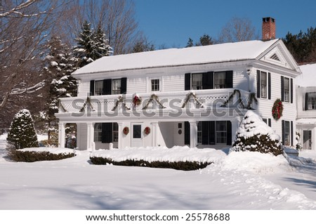 Attractive white house in vermont, covered with snow.