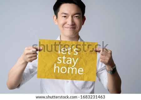 attractive white shirt asian male smile hand hold paper with sentence let stay home in covid-19 spread and tell everyone to quarantine or work from home healthy ideas concept gray background