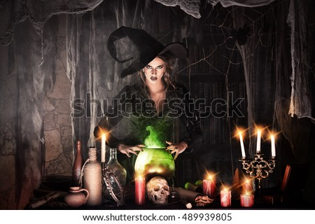 Attractive witch conjures in the wizarding lair. Fairytales. Halloween. #489939805
