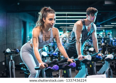 Attractive woman and handsome man doing spinning on cycling bikes #1337436224