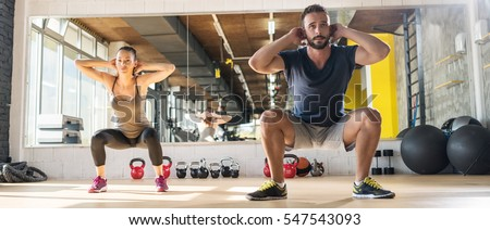 Attractive woman and man exercising at gym.