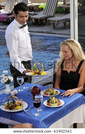 Attractive woman at a restaurat having dinner being served by a waiter - a series of RESTAURANT images.