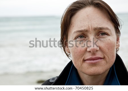 Attractive woman at beach with thoughtful expression.