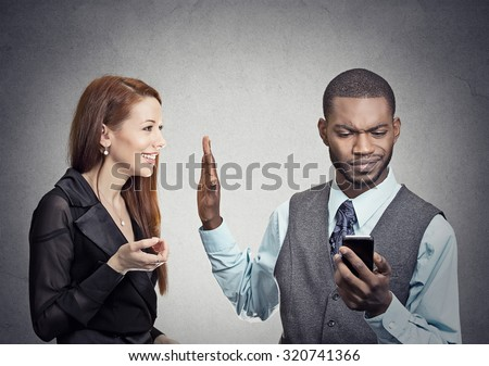Attractive woman being ignored stopped by young handsome man looking at smartphone reading browsing internet isolated on gray wall background. Phone addiction concept. Human face expression emotions  Stock photo ©