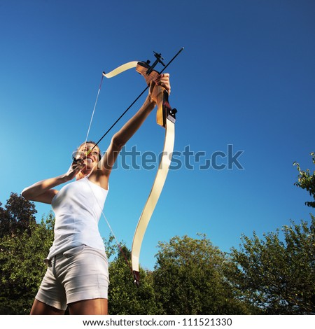Attractive woman bending a bow and aiming in the sky