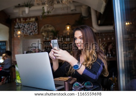 Attractive woman blogger publication article in social network via mobile phone after distance work on laptop computer, sitting in modern coffee shop interior. Pretty female content manager using apps