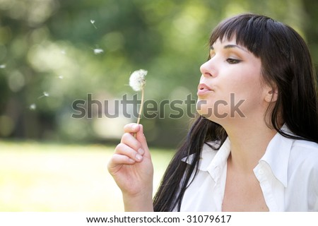 attractive woman bloweing dandelion at meadow
