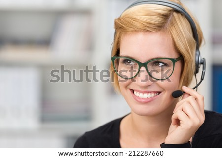 Attractive woman call centre operator wearing heavy framed glasses and a headset smiling as she listens to a conversation with a customer