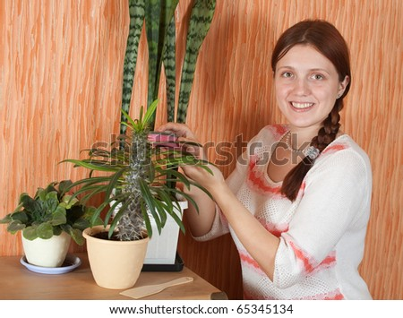 Attractive woman cleaning flowers in the pot at her home