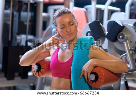 attractive woman cooling herself with water bottle in gym