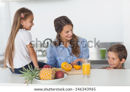 Attractive woman cutting an orange for her children in the kitchen
