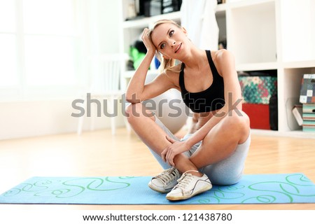 Attractive woman do fitness exercise at home on a blue mat
