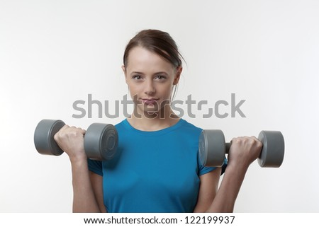 attractive woman doing a workout routine with a  dumbbell weights
