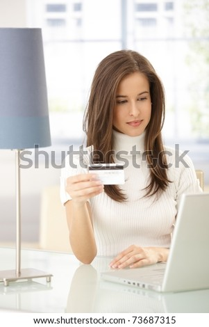 Attractive woman doing electronic shopping online with credit card.?