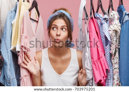 Attractive woman dressed casually, looking with doubts aside while standing near hangers with clothes, thinking what to dress on business meeting with companions. Woman of fashion having many clothes