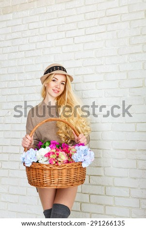 Attractive woman dressed in a sweater and cap holding a basket of flowers. Girl smiling, standing at a brick wall. The concept of innocent beauty.